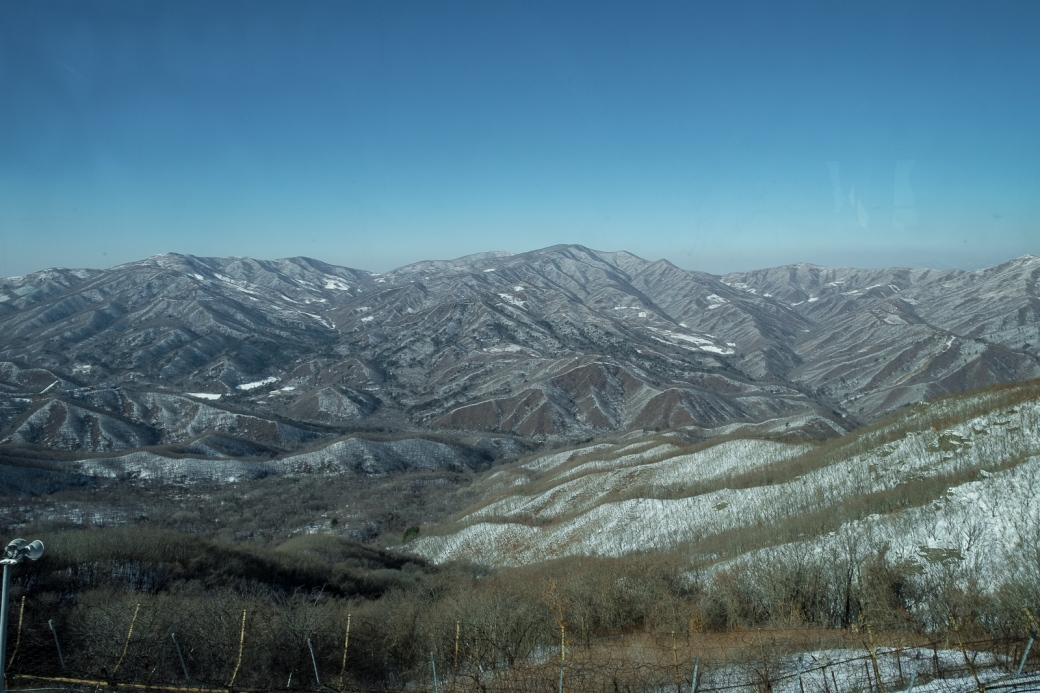 20170201-7782 A view into North Korea, through terrible tinted glass and trying to avoid a soldier shouting at me for taking photos when I wasn't alllowed to. From the DMZ observatory
